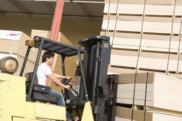 mid-adult man driving forklift