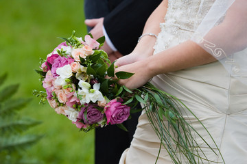 Bride and groom stand near each other with bouquet of roses