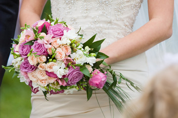 Bride with beautiful bouquet of roses and other wedding flowers