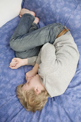 young blond sad man lying on the bed.