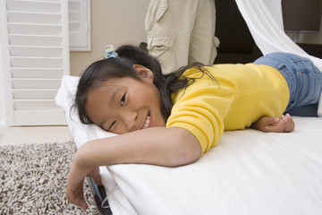 Girl lying down on bed and smiling