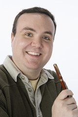 Portrait of mid-adult man holding pen, smiling