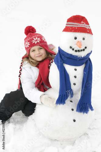 Little girl playing with snowman