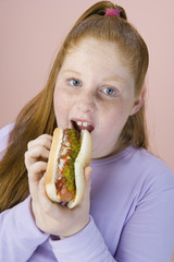 Overweight girl eating hot dog, portrait