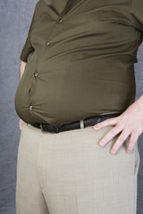 Overweight mid-adult man with hands on hips, mid section
