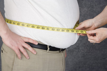 Woman measuring waist of overweight  man with tape measure, middle section