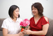 Asian mum receiving bouquet of red and pink roses