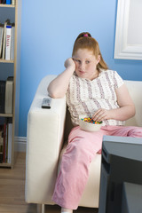 Overweight girl watching television on sofa