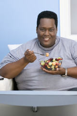 Man Eating Bowl of Fruit