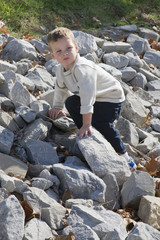 Little boy climbing rocks