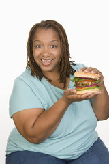 Portrait of Mid-adult overweight  woman holding big cheeseburger and smiling