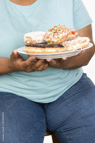 Mid-adult overweight  woman holding plate with donuts.