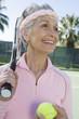 Senior woman holding tennis racket and balls