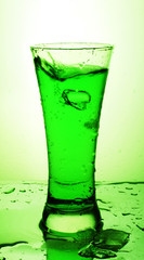 Glass with green beverage and ice