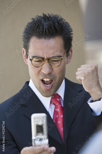Excited business man holding mobile phone, outdoors