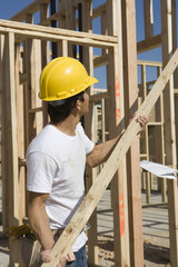 construction worker holding plank