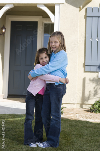 Portrait of girls 609 hugging in front of house