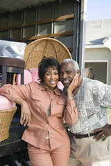 Middle-aged couple in front of lorry with furniture