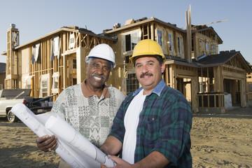 Two men holding blueprints at construction site, portrait