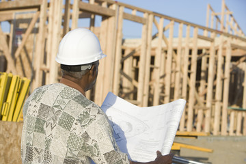 Middle-aged man with blueprints, construction site, back view