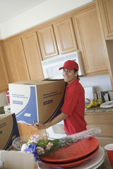 Man carrying a box in kitchen