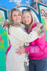 Two blonde girlfriends embrace on a background of graffiti