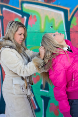 Two blondes are fighting against a background of graffiti