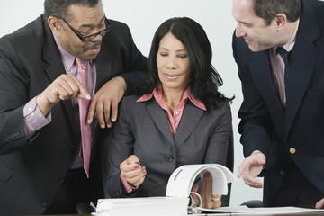 Three businesspeople looking at documents