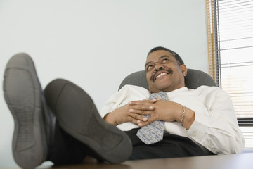 Mature businessman with his feet up