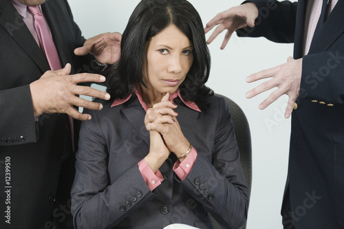 Two businessman grabbing a businesswoman