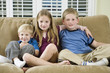 Portrait of three children sitting on a sofa.