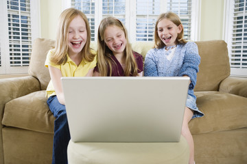 View of three friends looking at a laptop.