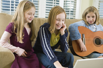 View of three girls operating a laptop.