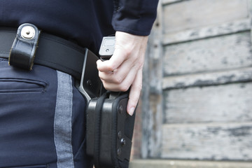Police woman drawing handgun from holster..
