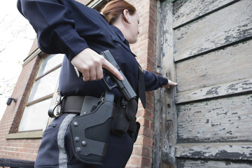 Female police standing outside the door with a gun..