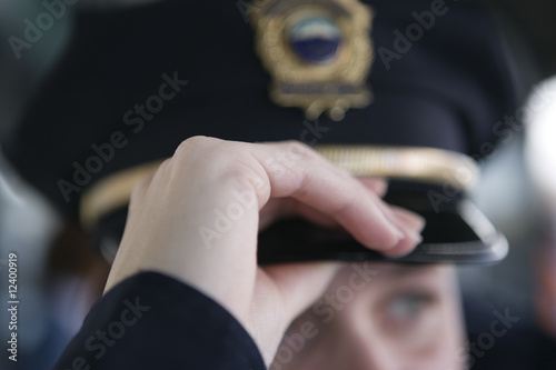 Close up of a female police woman's hand adjusting cap..