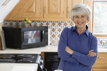 Portrait of a cheerful woman standing in a kitchen.