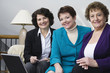 View of smiling business women sitting with a laptop.