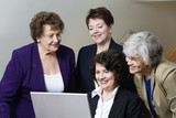 View of smiling business women looking at a laptop.
