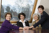 Portrait of smiling business women sitting by a table.