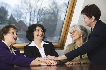 View of smiling business women conversing with each other.