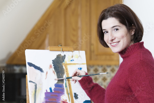 Smiling young woman painting on a drawing paper.