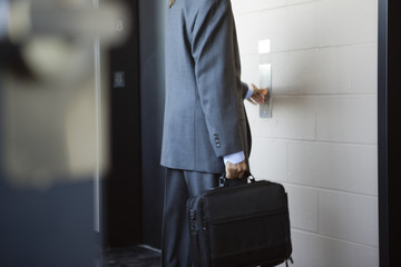 A young Business man pushing button of an elevator.