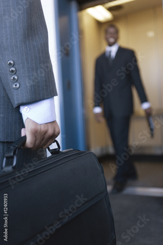 Close up of a business man holding a briefcase.