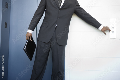 A young business man pressing push button of an elevator.