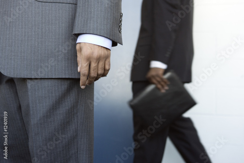 Two businessmen standing by a wall.