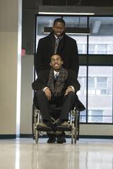 A businessman helping his colleague in a wheelchair.