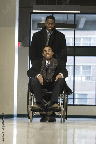 A businessman helping his colleague in a wheelchair.
