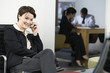 Business woman on cellphone with business colleague