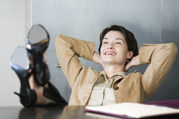 Business woman relaxing in office with her legs on the desk.